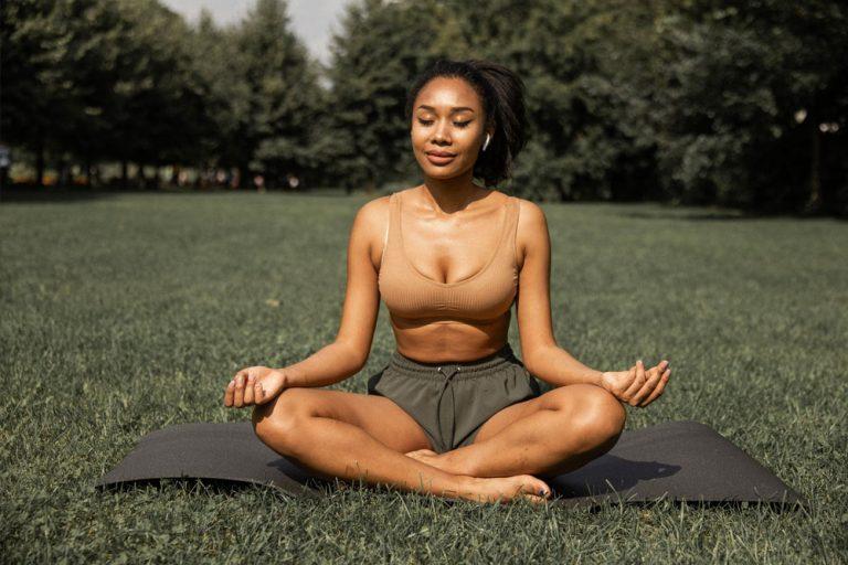 woman meditating on lawn