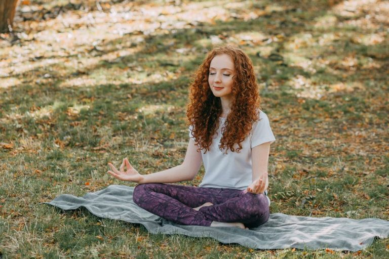 young woman meditating on grass