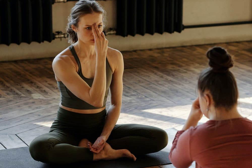 two women meditating and pointing toward third eye location